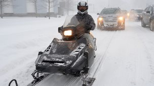 A man driving a snowmobile.