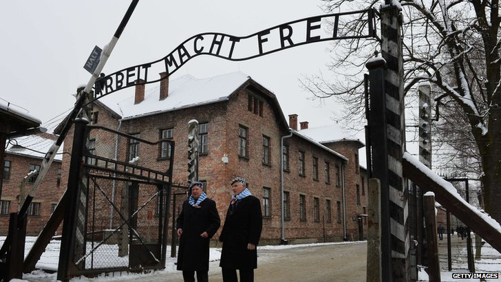 Holocaust survivors walk through the gate of the former Auschwitz concentration camp on 27 January 2015