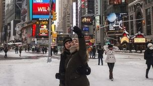 A woman takes a photograph of herself in New York's Times square (27 January 2015)