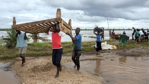 Members of a family displaced by recent floods belongings as they arrive at M'bwazi Primary School after crossing the flooded Ruo river in the area of Chief Mulolo in Malawi's southern Nsanje District on January 18, 2015.