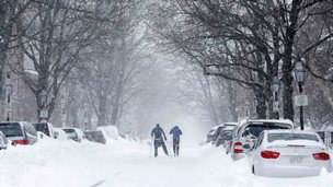 Two skiers on a road in Boston