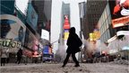 "A few tourists wonder around nearly deserted New York""s Times Square what is normally a crowed morning rush hour"