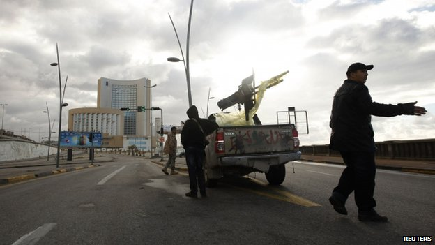 A vehicle belonging to the security forces is pictured near Corinthia hotel (rear) in Tripoli (27 January 2015)