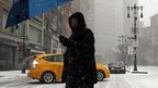 A man walks through the snowy streets of New York City.