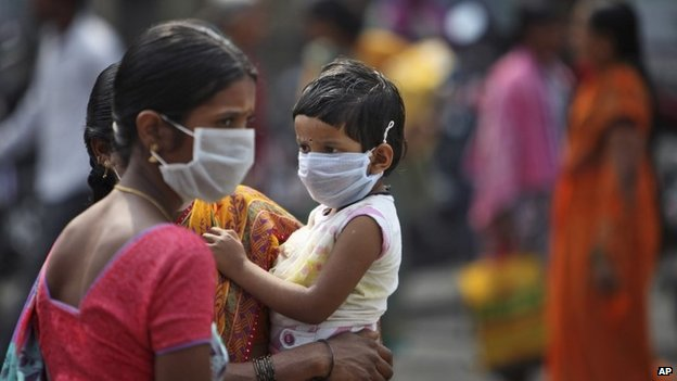An Indian woman and a child cover themselves with protective masks after the news of the outbreak of swine flu virus as they walk inside the premises of Gandhi Hospital in Hyderabad, India, Wednesday, Jan. 21, 2015.
