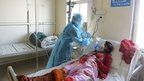 An Indian medical staff member treats a swine flu patient at an isolation ward of the Ahmedabad Civil Hospital in Ahmedabad on January 23, 2015.