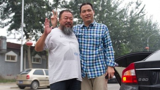 Chinese artist Ai Weiwei (L) stands with his lawyer Pu Zhiqiang as he leaves for court in Beijing on July 20, 2012.