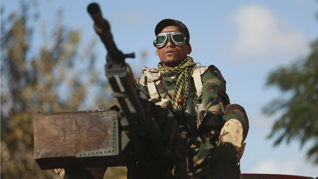 A personnel of pro-government Libyan forces, who are backed by locals, looks on during clashes in the streets with the Shura Council of Libyan Revolutionaries, an alliance of former anti-Gaddafi rebels, who have joined forces with the Islamist group Ansar al-Sharia, in Benghazi December 28, 2014
