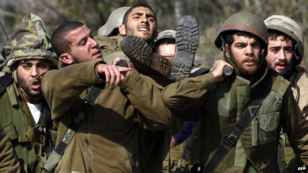 Israeli soldiers carry a wounded comrade near the Lebanese border (28 January 2015)