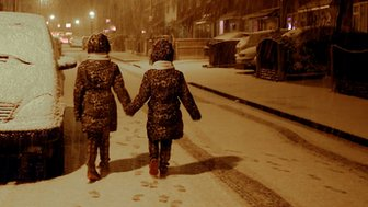 Girls hold hands in snow