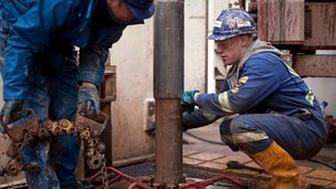 Fracking workers looking at drill