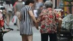 A daughter helps her elderly mother walking along a street in China