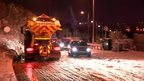 Gritter spreading salt on snowy road