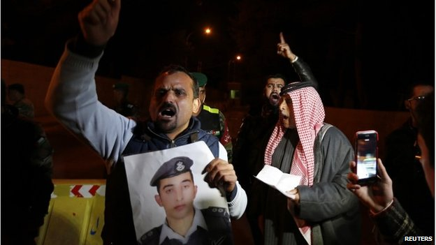 A relative of Jordanian pilot Moaz al-Kasasbeh holds his picture as relatives demand the government negotiate his release.