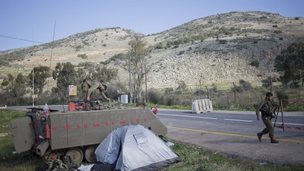 Israeli soldiers guard a road where a missile fired by the Lebanese Hezbollah group struck an Israeli military convoy on Wednesday.