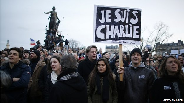 People holding cardboards reading 'Je suis Charlie (I am Charlie) take part in a Unity rally in the Place de la Nation (Nation Square) in Paris on 11 January 2015