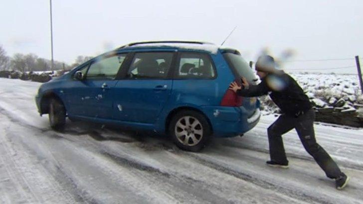 Man pushing car on road