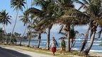 Two people walking along a road by the sea in American Samoa