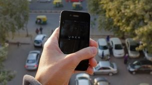 The Uber smartphone app, used to book taxis using its service, is pictured over a parking lot as auto-rickshaws (background) ply a road in the Indian capital New Delhi on December 7, 2014