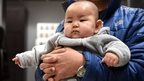 This picture taken on 19 January 2015 shows a Chinese baby in the arms of his father at a furniture store in Beijing