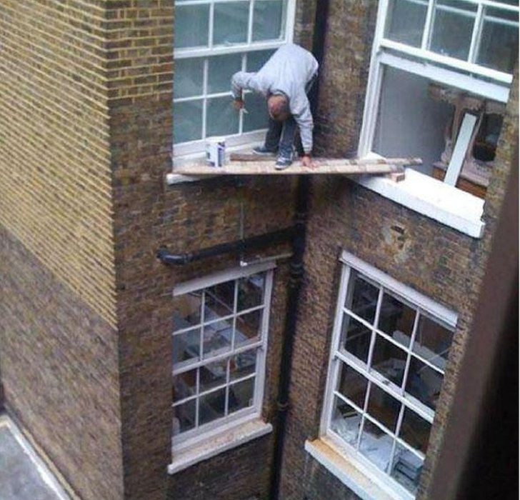 Painter doing window ledges over a great height, balancing on wooden boards between open windows