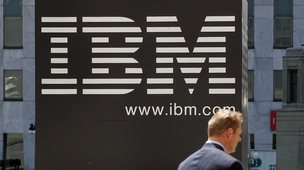 Man walking past an IBM sign