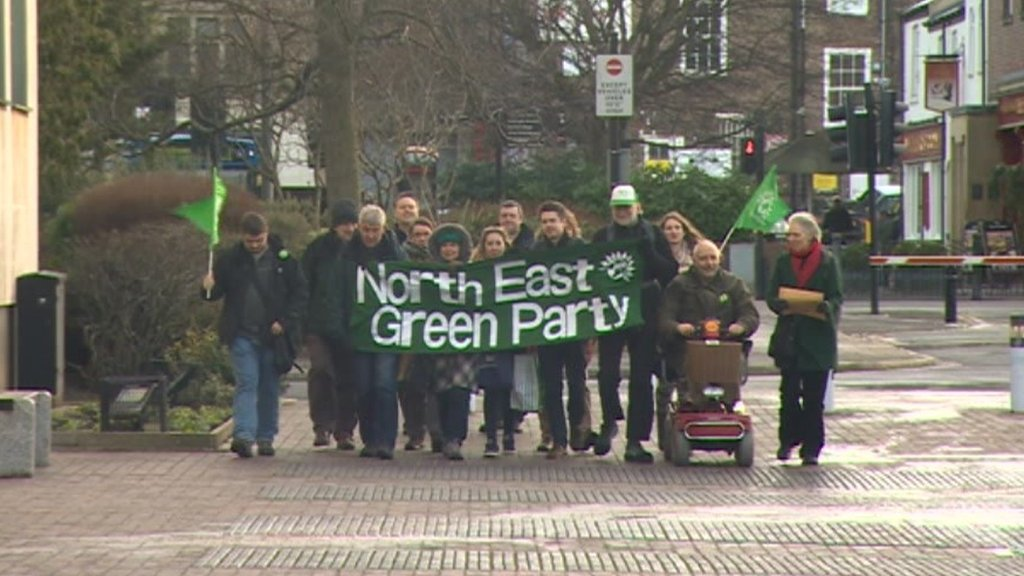 Green Party members marching with banner