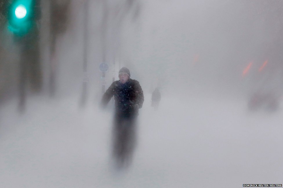 A man rides his bike up Beacon Street during a blizzard in Boston, Massachusetts