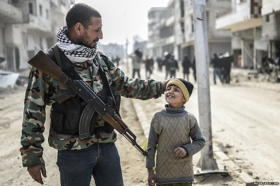 A Kurdish fighter walks with his child in the center of the Syrian border town of Kobane