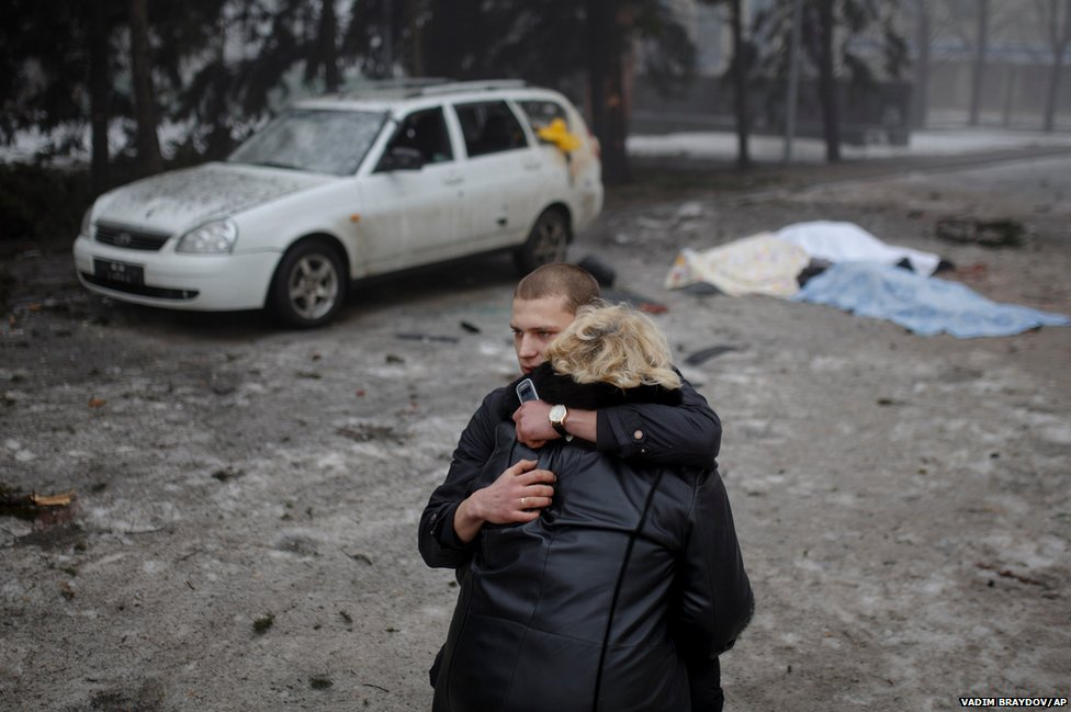 A rebel comforts the wife of a civilian killed by shelling in Donetsk, eastern Ukraine