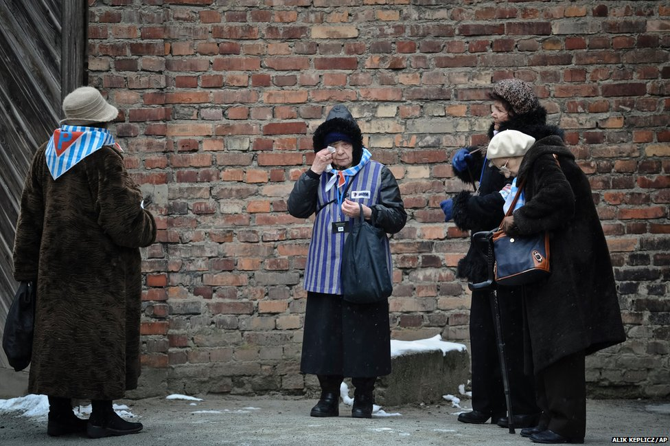 A Holocaust survivor wipes her eye while standing along with others outside a detention block of the Auschwitz Nazi death camp in Oswiecim, Poland