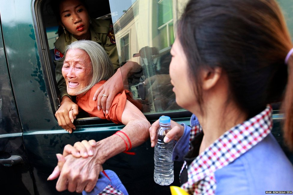 Eng Sokha holds her mother Nget Khun's hand as she is taken away in a police van