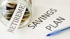 Jar of coins, pen and retirement and savings plan written on pieces paper