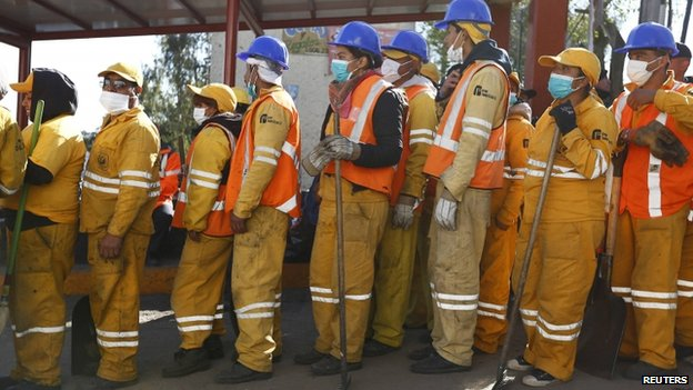 Crew members queue to prepare to clear debris the day after a deadly gas truck explosion ripped through a maternity hospital in Mexico City