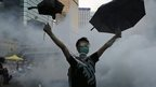 A protester (C) raises his umbrellas in front of tear gas