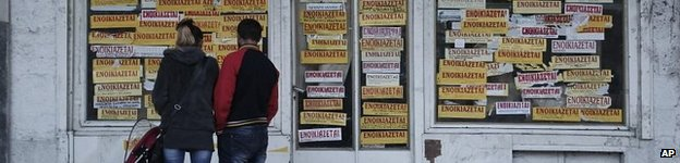 Greek couple look at adverts for rental properties
