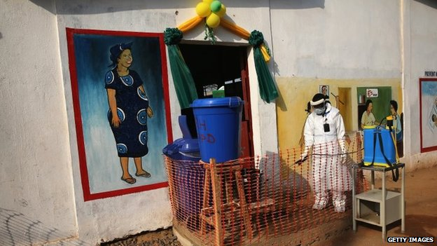 A health worker wearing protective clothing waits outside Redemption Hospital on 1 February 2015 in Monrovia, Liberia.