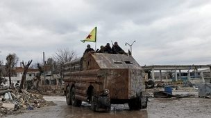 Members of Syrian Kurdish People's Defence Units (YPG) stand on the back of a homemade armoured vehicle as they patrol Kobane (30 January 2015)