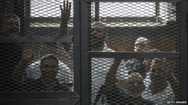 Egyptian Muslim Brotherhood leader Mohamed Badie (2nd right) and other defendants gesture during their trial in Cairo on 7 June 2014
