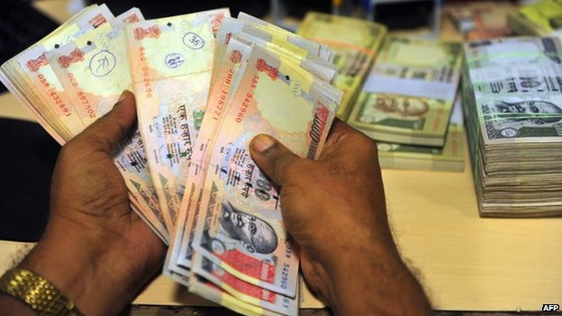 Indian rupee notes in a man's hands