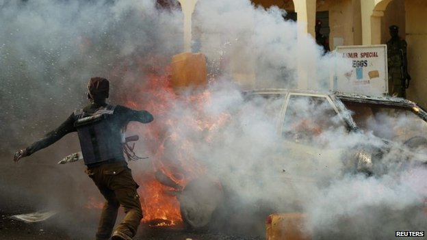 A man throws a container of water towards a burning car after a bomb explosion barely a few minutes after Nigerian President Goodluck Jonathan left Gombe stadium on 2 February 2015