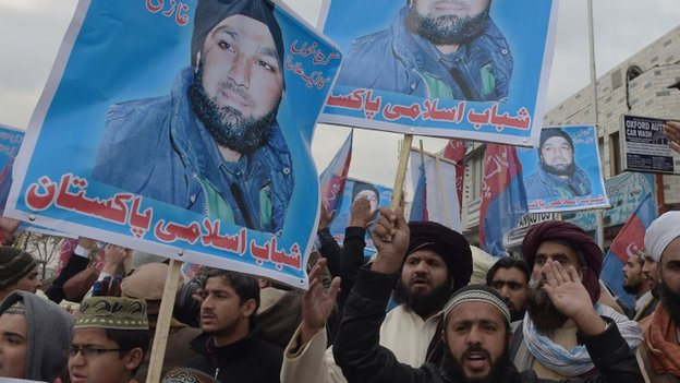 Pakistani Islamist and supporters of former police bodyguard Mumtaz Qadri, hold his portrait as they shout slogans calling for his release during a protest outside the high court building in Islamabad on February 3, 2015.