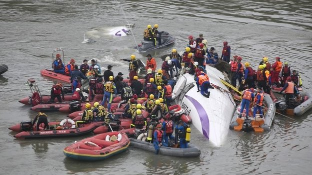 Rescue teams work to free people from a TransAsia Airways ATR 72-600 turboprop airplane that crashed into the Keelung River shortly after takeoff from Taipei Songshan airport on February 4, 2015 in Taipei, Taiwan.