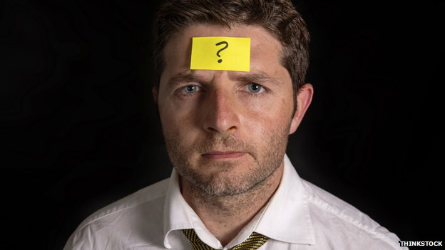 Man with Post-it note on his forehead, with question mark on it.