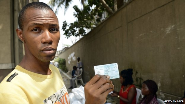 A voter shows his Permanent Voter's Card (PVC) after receiving it from officials of the Independent Electoral Commission in Lagos