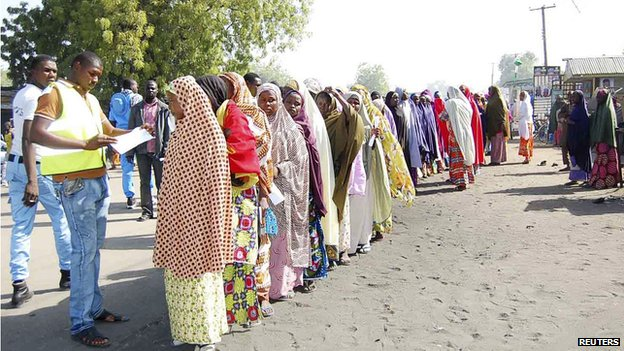 Displaced people fleeing from violence wait in line to receive relief materials at a camp for displaced people camp in Borno State