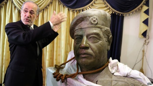 Mowaffak al-Rubaie with a statue of Saddam Hussein and the rope around its neck