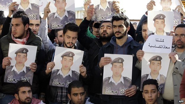 Activists carry posters with a portrait of the Jordanian pilot Muath al-Kassasbeh