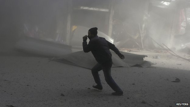 A man runs after an air strike reportedly carried out by the Syrian air force in the town of Douma