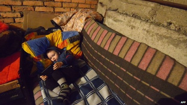 Michal, 4, lies on a makeshift bed as he and others wait for shelling to end in Donetsk's Petrovski district, in the eastern Ukraine on 4 February 2015